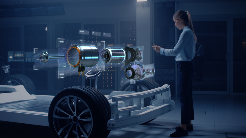 Female Automobile Engineer Using Digital Tablet with Augmented Reality Analyses Electric Engine Prototype. Innovative Facility: Vehicle Frame with Graphics Showing Motor Parts, Torque and Infographics