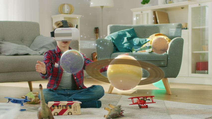 Smart Little Boy Wearing Augmented Reality Headset Plays with Space Learning Software, With Gestures He Manipulates 3D Planets, Discovers Facts About Solar System and Cosmos #1034861858