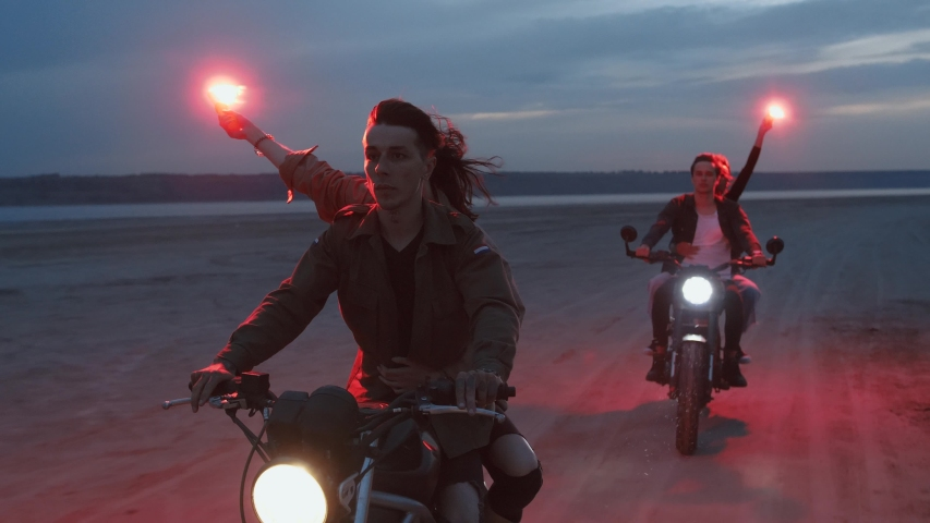 Two young couples riding on vintage motorcycles with red burning signal flares after sunset on beach, slow motion