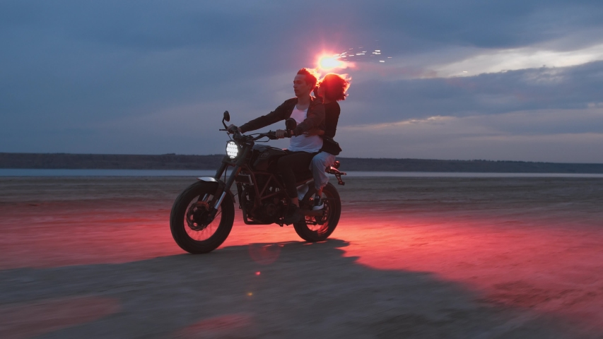Young couple riding on vintage motorcycle with red burning signal fire after sunset on beach, slow motion | Shutterstock HD Video #1034862842