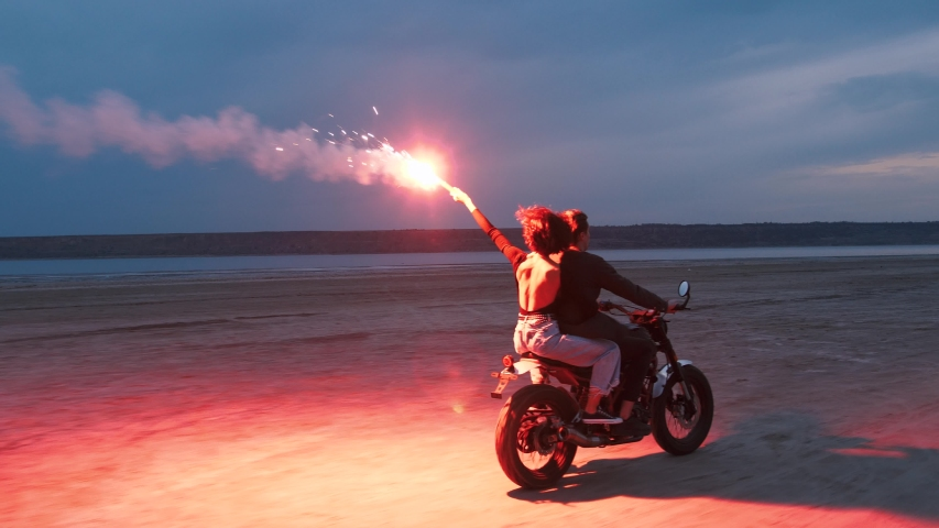 Couple riding on vintage motorcycle with red burning signal fire after sunset on beach, slow motion