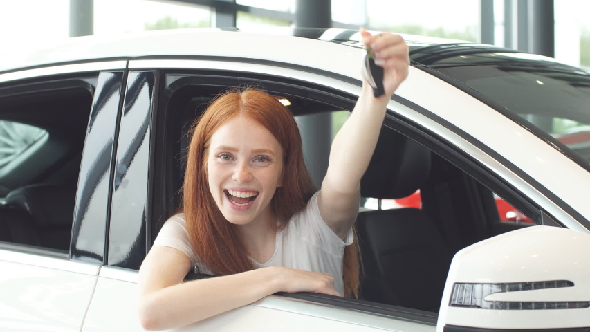 Happy ginger woman smiling at camera and showing new car key. Car Purchase or Rent concept