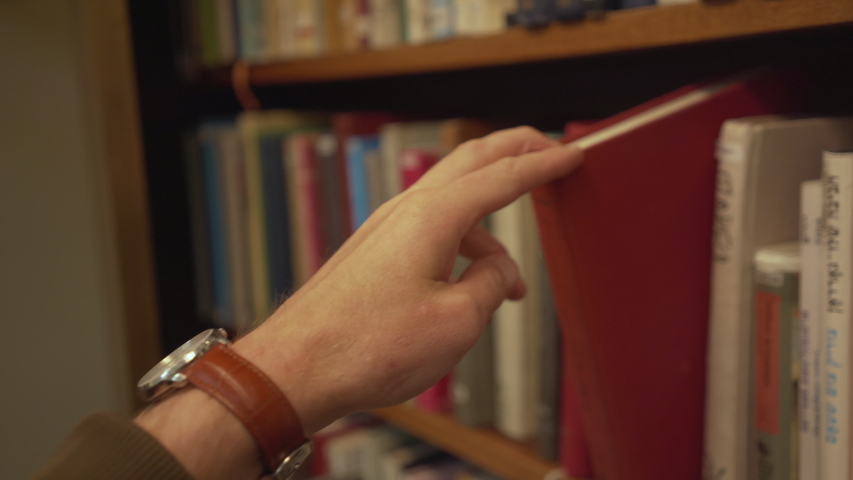 Hand reaches for and pulls books from bookshelf   Shutterstock HD Video #1034874362