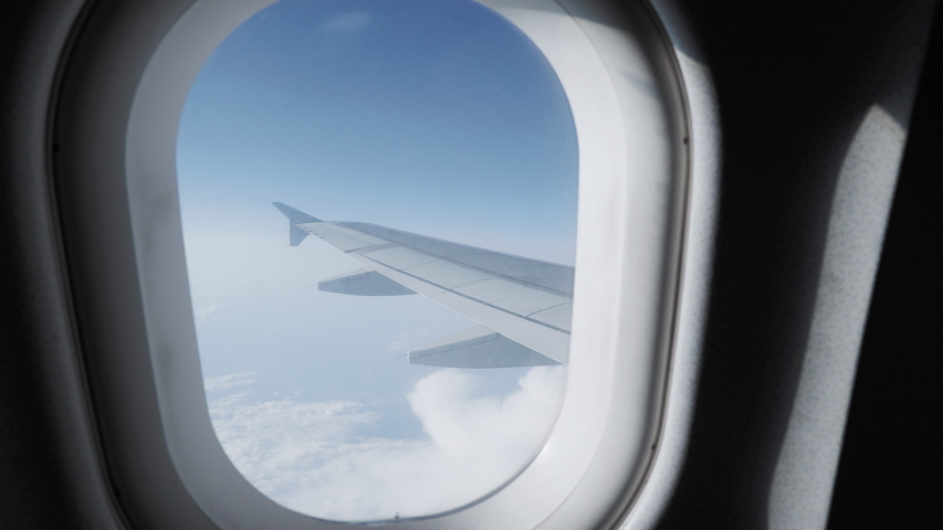 View on blue sky and fluffy white clouds through the window of the aircraft. Scenic view from flying airplane. #1034875154