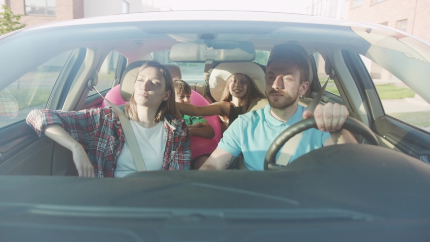 NEW YORK - April 5, 2018: Beautiful young family with kids traveling to the seaside by car. Front view of a loving cuouple and their siblings talking smiling sitting in the car. | Shutterstock HD Video #1034878265