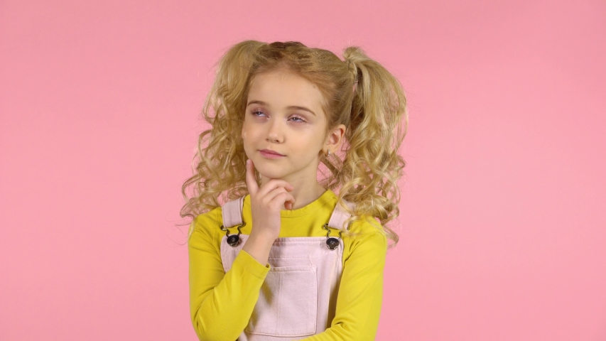 Pretty blond little girl is thinking and touching her face with her finger in studio on pink background. The girl is wearing a pink sundress with yellow bright jumper, she has two ponytails and curly | Shutterstock HD Video #1034883746