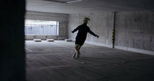 HANDHELD Teenager girl soccer player practicing kicks and moves inside empty covered parking garage. 4K UHD 60 FPS RAW graded footage