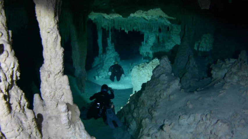 2 cave divers in cenote Pet Cemetery traveling between rock formations - Cave system Sac-Aktun, Mexico. | Shutterstock HD Video #1034914886