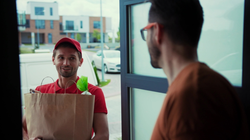 Convenient home food delivery. Side view of happy courier delivering food from supermarket. Male customer receiving food bag paying for order with credit card. Royalty-Free Stock Footage #1034918849