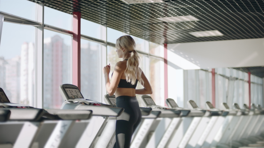 Fitness woman running on treadmill in gym. Athlete woman using run machine in fitness center. Pretty girl having cardio training in sport club.