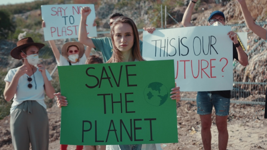 Young activists in action against pollution stay at landfill site. Focus on young woman holding climate strike poster at protest strike. Save the Planet. | Shutterstock HD Video #1034925833
