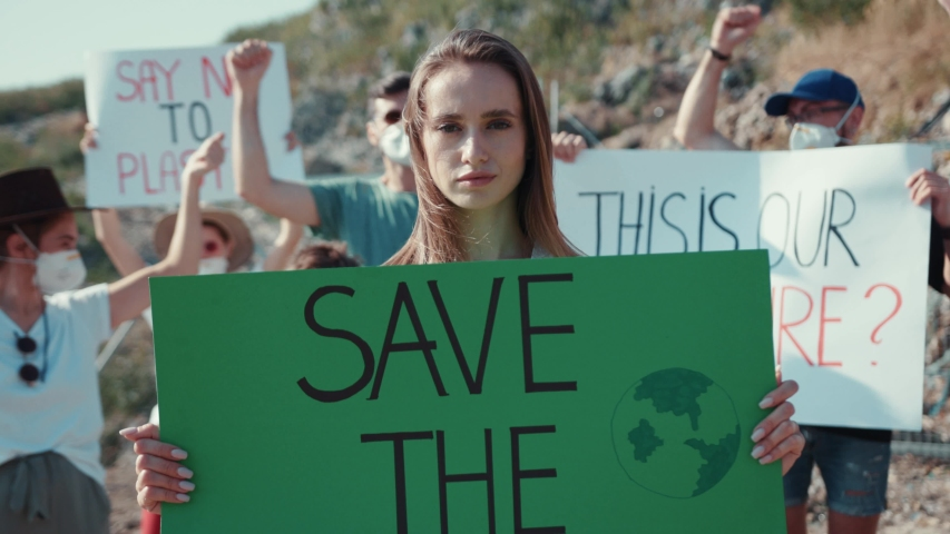 Outdoor portrait of woman activist with Save the Planet ecology poster. In background fighting people protesting against garbage pollution staying at dump in city outskirts. | Shutterstock HD Video #1034925989
