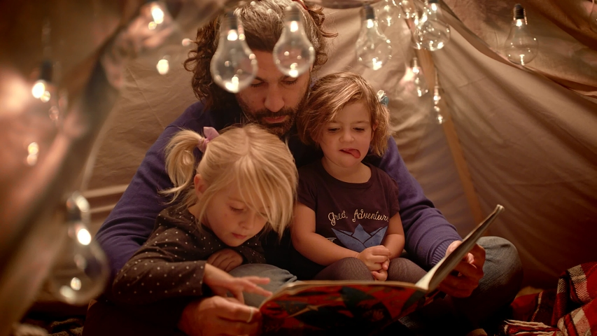 Happy daddy and little daughters read a book in a tent at home