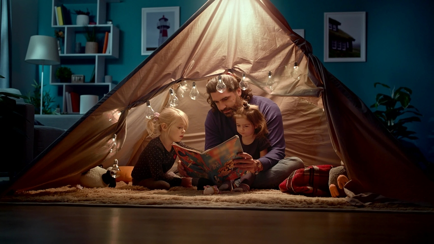 Happy dad and little daughters read a book in a tent at home