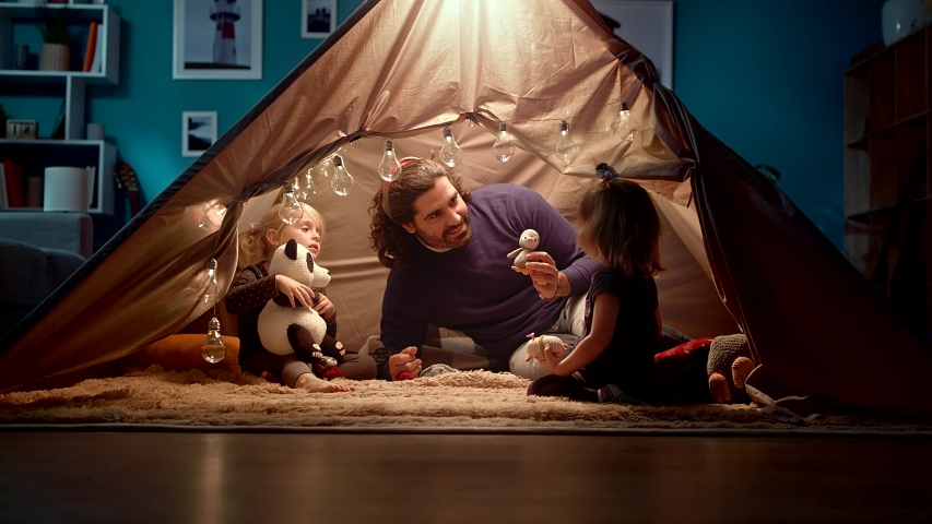 Dad with daughters in a tent at home. Dad imitates a penguin. | Shutterstock HD Video #1034959082