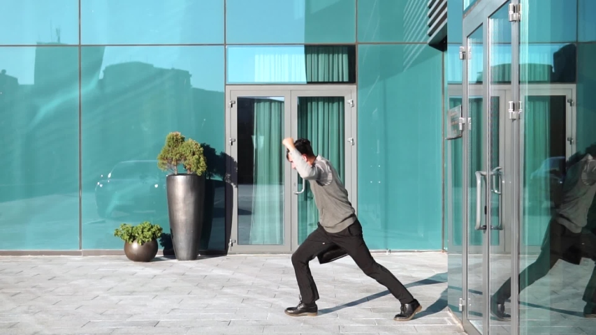 After a successful deal, a young businessman with a briefcase fools around, throws up his briefcase and has fun. Slow motion | Shutterstock HD Video #1034971781