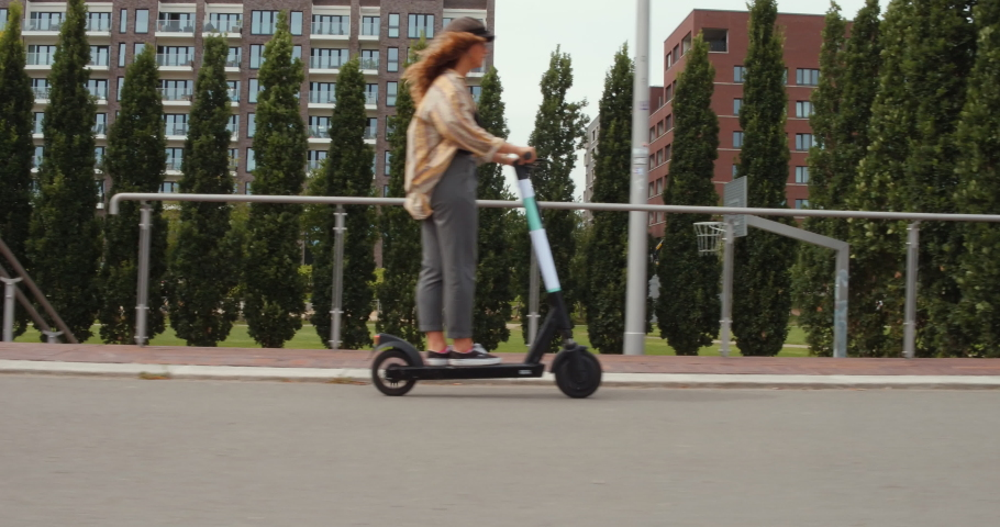 Girl rides an electric scooter or e-scooter roller in hamburg city germany, ecological e mobility in the urban city, 4k Steady Parallel Side Shot, modern transportation