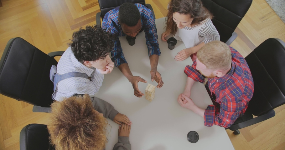 Top view of colleagues of mixed ethnicity playing board games and take wooden blocks out of tower Royalty-Free Stock Footage #1035021539