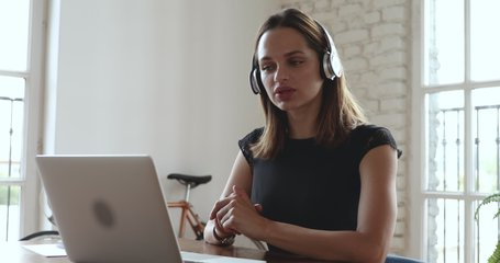 Smiling young business woman receptionist wear wireless headphone video conference calling on laptop computer talk by webcam in online chat, customer support service and online study teaching concept