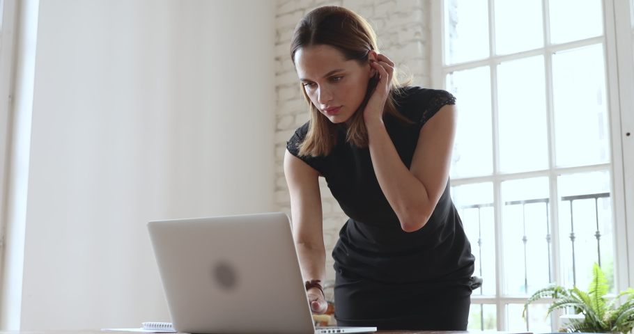 Focused young business woman professional entrepreneur using laptop computer notebook at workplace typing email making notes standing at desk working doing online job in modern corporate office | Shutterstock HD Video #1035023870