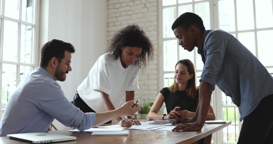 Young creative african and caucasian colleagues group analyze paperwork talk work together at diverse team meeting, focused friendly business team brainstorm on project strategy at briefing table Royalty-Free Stock Footage #1035023942