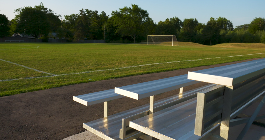 Bleachers overlooking an empty soccer field on a sunny, summer morning