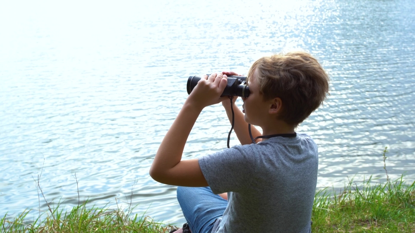 Closeup view of white kid exploring nature outside sitting at shore of river. Real time 4k video footage.