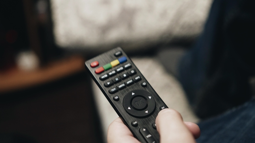 A man holding a TV remote lying on the couch. Atmosphere of rest.