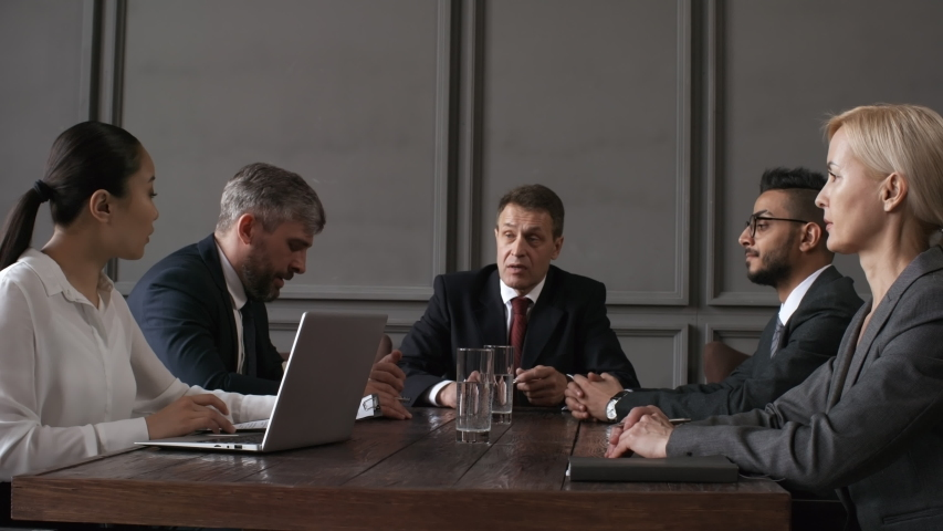 Waist-up shot of four corporate executives in business formal attire sitting around table at corporate meeting, CEO asking secretary to pass around minutes, and each director signing on document Royalty-Free Stock Footage #1035040169