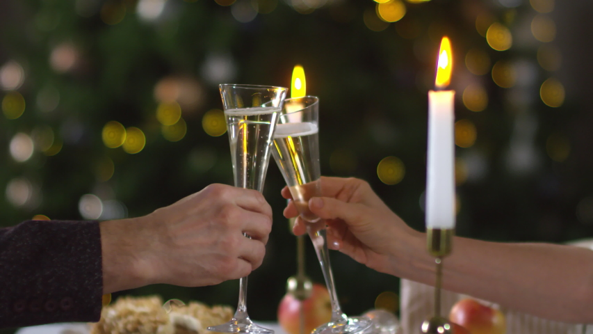 Close-up hands shot of unrecognizable man and woman clinking glasses with champagne over festive dinner with candles, and decorated Christmas tree in blurred background | Shutterstock HD Video #1035068993