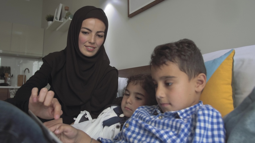 Young Arab mother in traditional dress is engaged in preschool activities