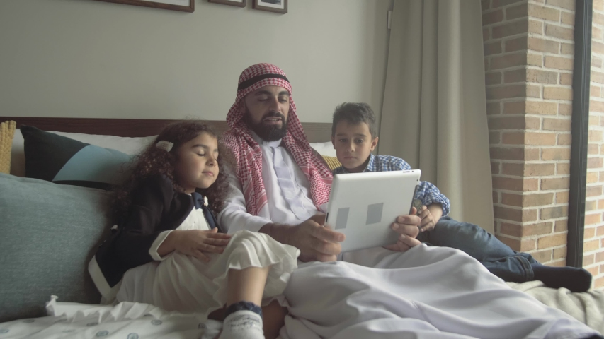 Arab father in traditional dress watches with children fascinating video