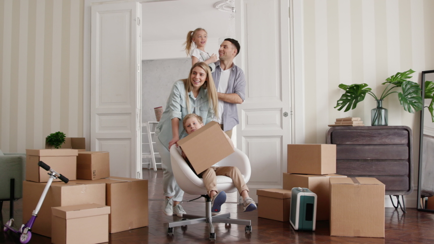 Active Homeowners Move in Rental Large Flat. Smile of Small Child Riding a Chair. Carton Packaging of Positive Relocating. Laughing Mom and Caucasian Dad Enjoy Life. Cute Emotion of Two Little Babies #1035079478