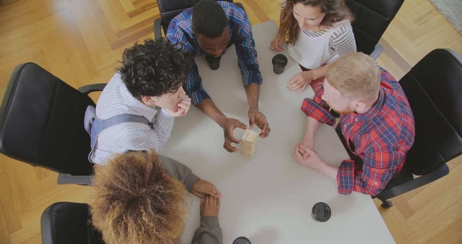 Top view of colleagues of mixed ethnicity playing board games and take wooden blocks out of tower Royalty-Free Stock Footage #1035086789