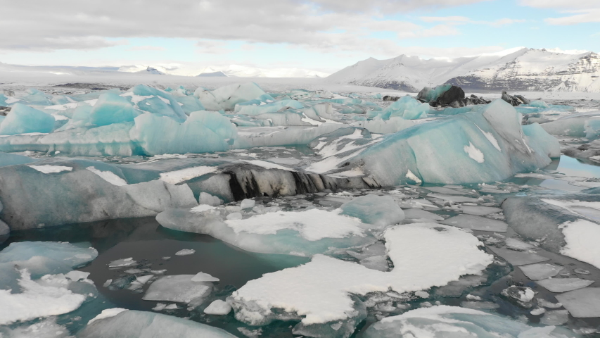 Aerial view flying over stunning icebergs floating in Jokulsarlon lagoon, dramatic natural Winter landscape (and powerful message of climate change) in Iceland  Royalty-Free Stock Footage #1035087881