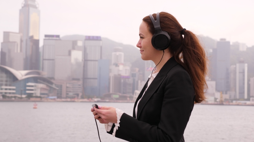 Business lady (model released) enjoy Victoria Harbour view, listen music from smartphone at large earphones. Blurred Hong Kong Island waterfront seen on background. Woman rest alone at beautiful place | Shutterstock HD Video #1035103316