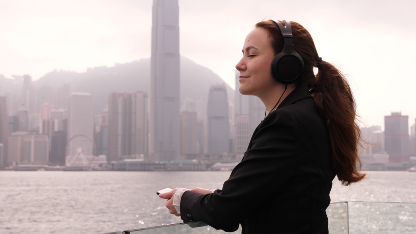Attractive business woman (model released) stay with eyes closed at Victora Harbour embankment, listen music on headphones. Lady rest at vacant time, recreate oneself with lovely audio tracks | Shutterstock HD Video #1035103337