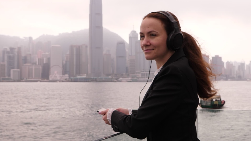 Adorable woman (model released) stay at Victoria Harbour, listen music at headphones, super slow motion shot. Business lady enjoy free time while travelling to Hong Kong with duty trip. | Shutterstock HD Video #1035103340
