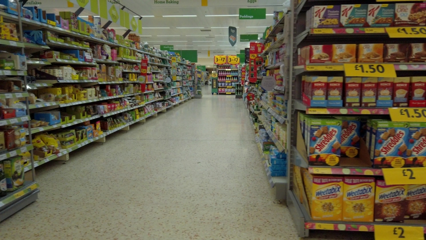 Widnes / United Kingdom (UK) - 06 22 2019: Empty supermarket aisle passing various selection of foods & goods.