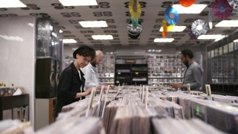 Medium arc shot of diverse customers perusing merchandise in record shop, and young curly Caucasian hipster woman wearing bowler hat and stylish glasses looking through vinyls in alphabetical order