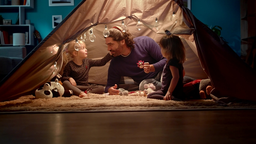 Dad with daughters in a tent at home. Dad imitates a owl.