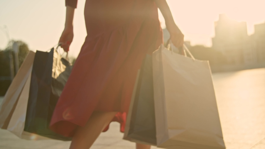 Woman in red dress with shopping bags walking in a city at sunset. Slow motion #1035131027