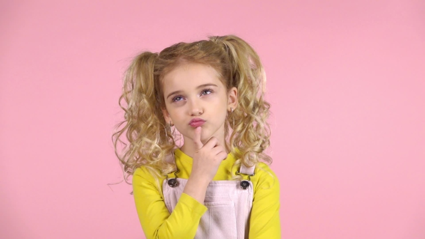 Young blond female is concentrated on thinking about something with cute blond hair in two ponytails and touching her face with finger, wearing yellow jumper, sundress at pink background. Slow motion | Shutterstock HD Video #1035136883