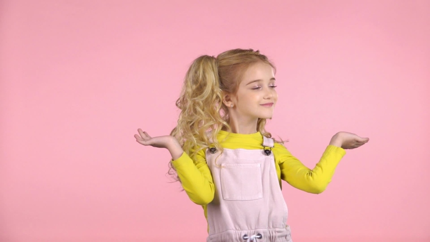 Beautiful sweet little girl is smiling and playing with her hair in the studio on pink background. She is wearing pink dress over yellow jumper. Slow motion | Shutterstock HD Video #1035136910