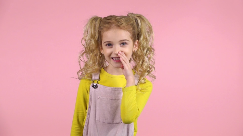 Beautiful little female is telling a secret with her hand near mouth in the studio on pink background. She has two cute ponytails. She is wearing pink dress and yellow jumper. Slow motion | Shutterstock HD Video #1035136940