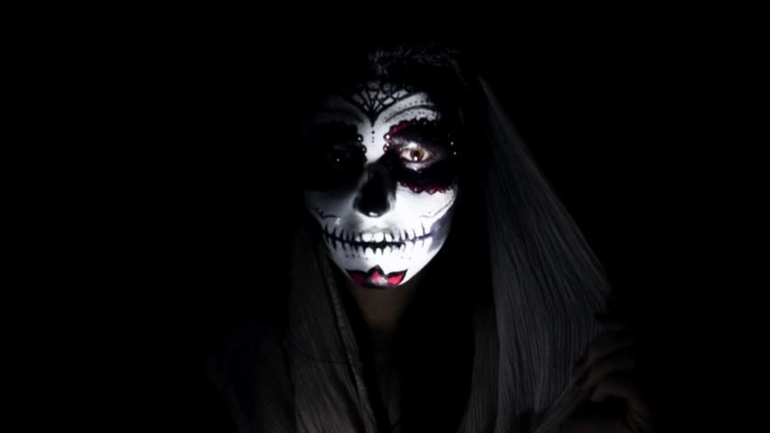 Halloween mask CALAVERA CATRINA. A girl in a blinking and frightening light. Mexican day of the dead. Portrait of a young woman with scary multi-colored makeup for Halloween on a dark background. 4K