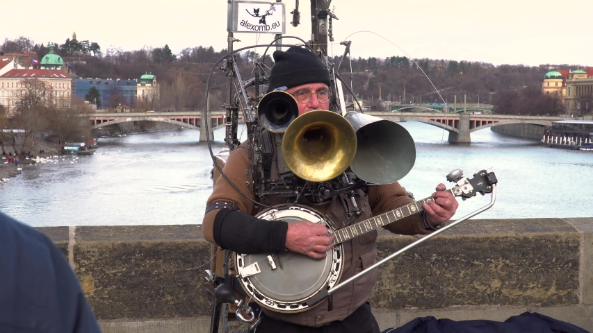 Prague / Czech Republic - 02 09 2019: Artistic, musical, one man band performance playing multiple horn & banjo instruments on urban, Prague cityscape bridge over flowing river.