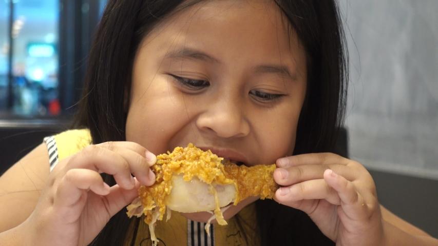 Cute little a girl eating fried chicken in a restaurant | Shutterstock HD Video #1035144995
