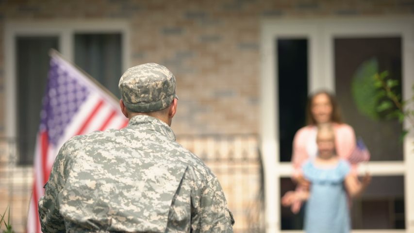 Daughter running to embrace father soldier, happy homecoming, holding US flag