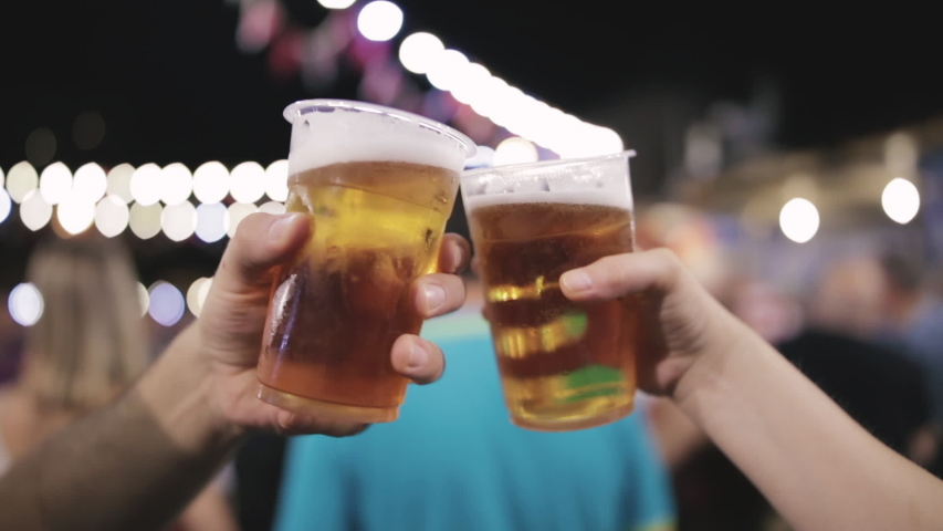 Friends drinking beer at night with de-focused lights in the background. Shallow focus. | Shutterstock HD Video #1035194723